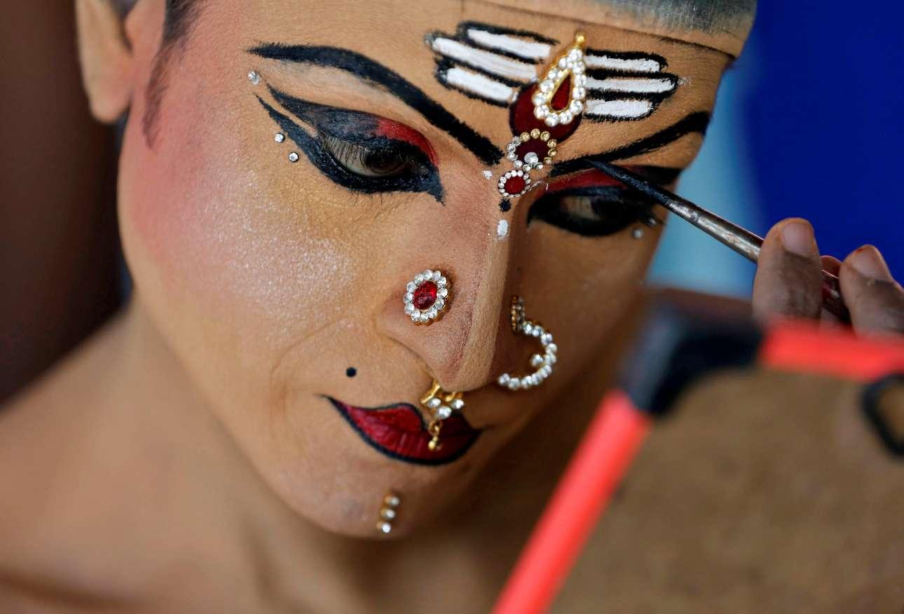 Τρίτη, 1 Ιανουαρίου, Ινδία. Ενας άντρας βάφεται λίγο πριν ξεκινήσει το 35ο Καρναβάλι Cochin για την υποδοχή του νέου έτους, στο Fort Kochi της Κεράλα