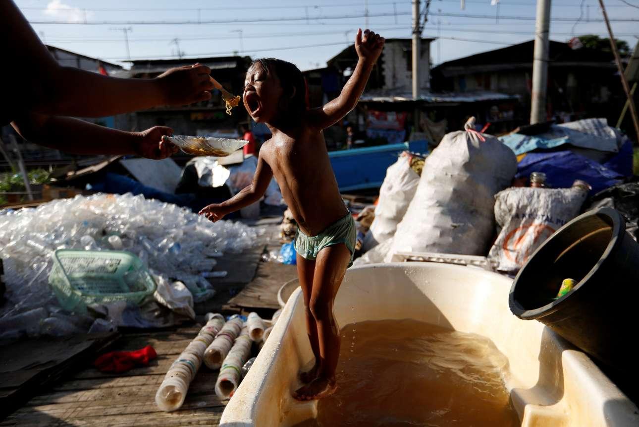 Παρασκευή, 4 Ιανουαρίου, Ινδονησία. Ενα παιδί τρώει ενώ παίζει, στα προάστια της Τζακάρτα, μιας από τις πλέον υποβαθμισμένες πρωτεύουσες στον κόσμο