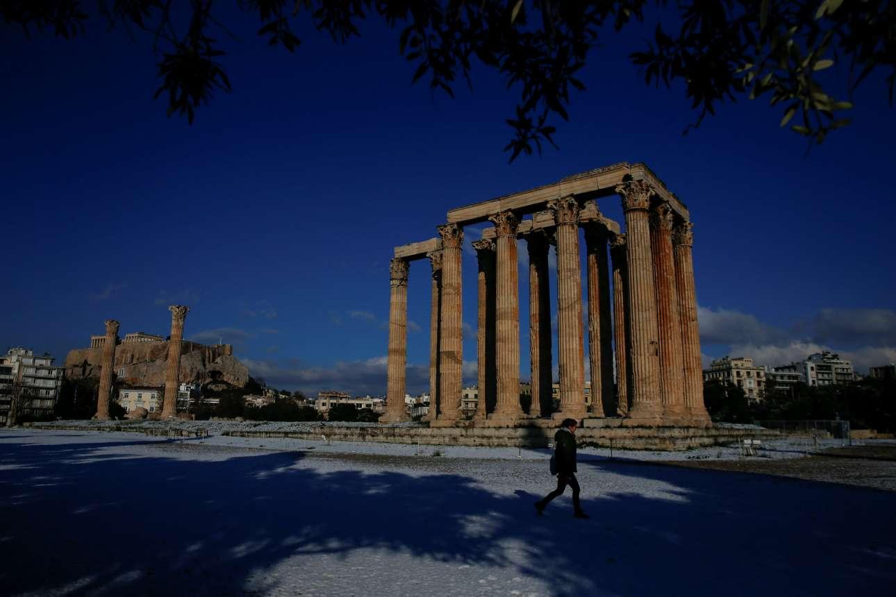 Μια κοπέλα προσπερνάει τον Ναό του Ολυμπίου Διός βαδίζοντας στο χιόνι. Αριστερά στο βάθος ο Ιερός Βράχος της Ακρόπολης