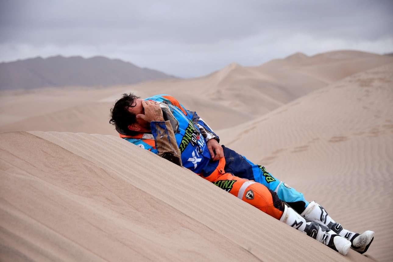 Ο βραζιλιάνος Μάρκος Κολβέρο ξαπλώνει απελπισμένος πάνω σε αμμόλοφο μετά τη συντριβή της  KTM μοτοσικλέτας του, στο τρίτο στάδιο του Ράλι Ντακάρ