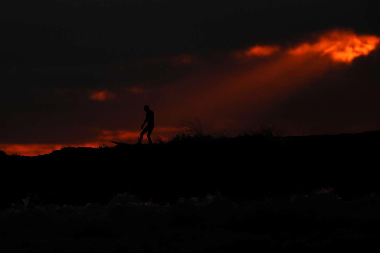 Πέμπτη 10 Ιανουαρίου. Ανδρας κάνει σερφ στη συννεφιασμένη παραλία του Κάρντιφ στην Καλιφόρνια, την ώρα που ο ήλιος δύει