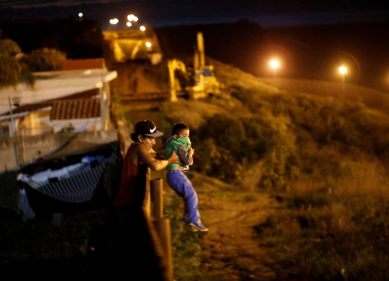 Δευτέρα, 14 Δεκεμβρίου, Μεξικό. Μετανάστης από την Ονδούρα που συμμετέχει στο μεταναστευτικό καραβάνι βοηθά ένα παιδί να περάσει τα σύνορα του Μεξικού με τις ΗΠΑ, στην Τιχουάνα