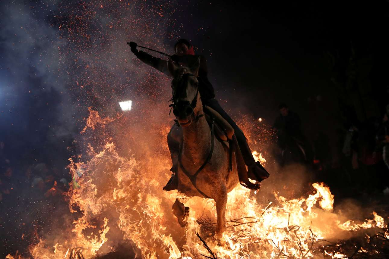 Πέμπτη, 17 Ιανουαρίου, Ισπανία. Μία γυναίκα περνάει καβάλα σε άλογο μέσα από τις φλόγες κατά τον εορτασμό του εθίμου που αποκαλείται Luminarias στο χωριό San Bartolome de los Pinares. Πρόκειται για τελετουργικό που πραγματοποιείται το βράδυ πριν από την γιορτή του Αγίου Αντωνίου και χρονολογείται τουλάχιστον από το 1500 μ.Χ.