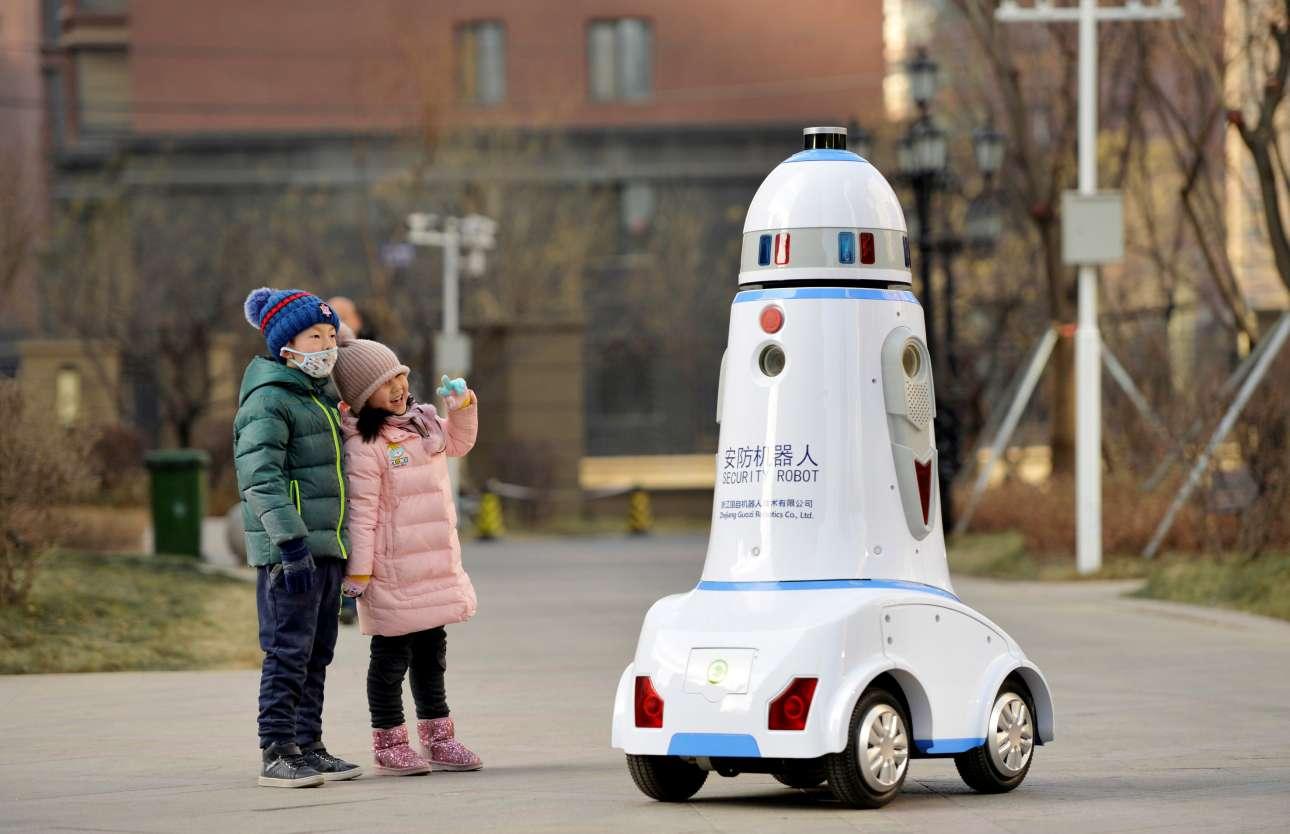 Παρασκευή, 18 Ιανουαρίου, Εσωτερική Μογγολία, Kίνα. Δύο παιδιά δίπλα σε ένα ρομπότ-αστυνομικό σε δρόμο της πόλης Χοχότ