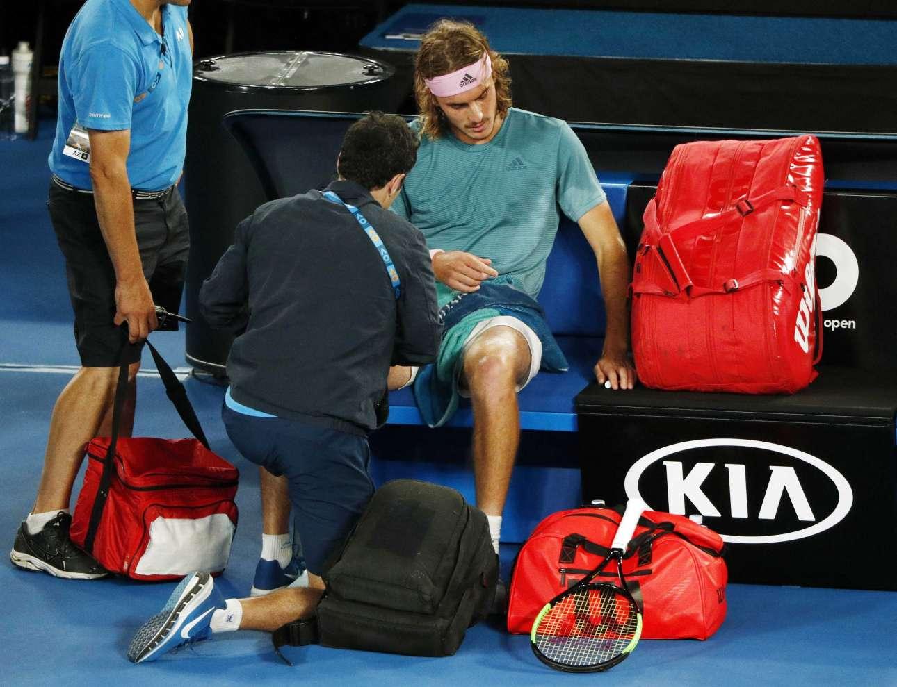 Ο Τσιτσιπάς δέχεται τις φροντίδες του γυμναστή κατά τη διάρκεια της ανάπαυλας