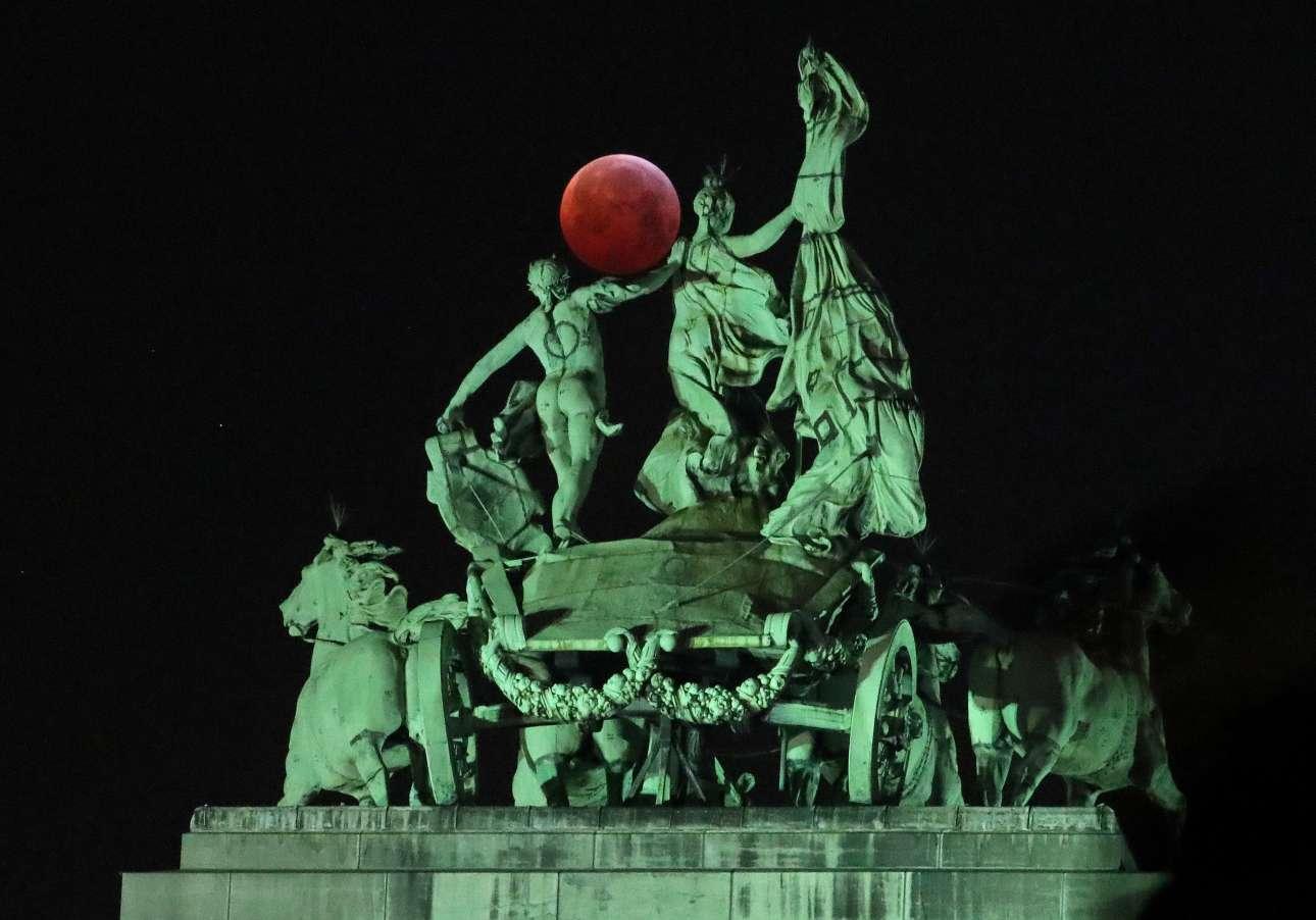 Σαν να είναι μέρος του αγάλματος μοιάζει η Σελήνη έτσι όπως διακρίνεται πίσω από την Αψίδα του Θριάμβου, στο πάρκο Σενκαντενέρ των Βρυξελλών