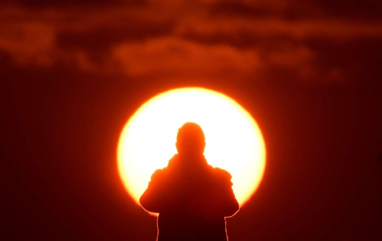 Δευτέρα, 21 Ιανουαρίου, Μεγάλη Βρετανία. Ενας περαστικός απολαμβάνει την ανατολή του Ηλίου στο Λονδίνο