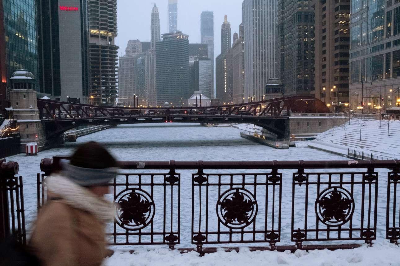 Γυναίκα περνά βιαστικά από γέφυρα πάνω από τον ποταμό του Σικάγου