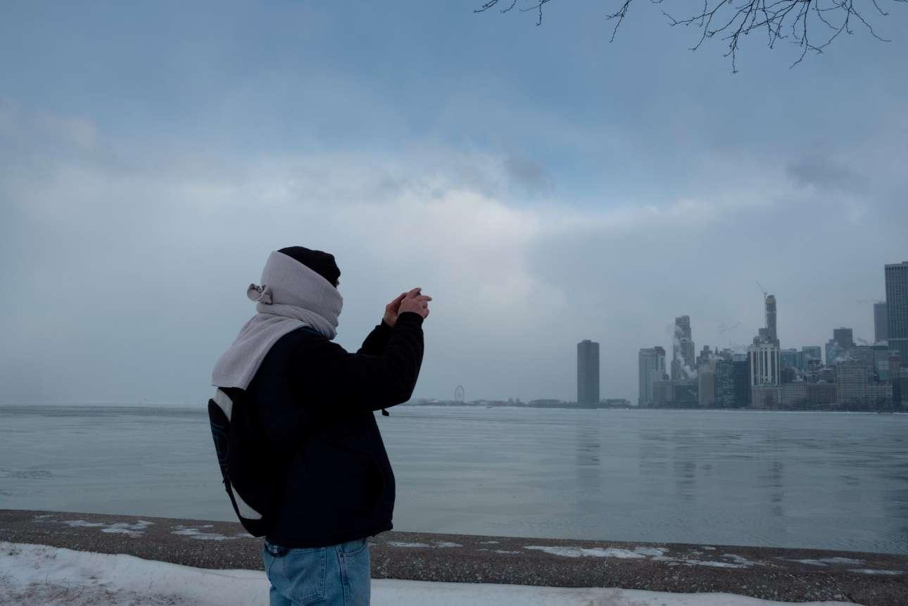 Ενας άνδρας φωτογραφίζει τους ουρανοξύστες του Σικάγου ενώ στέκεται λίγα μέτρα από την Λίμνη Μίσιγκαν