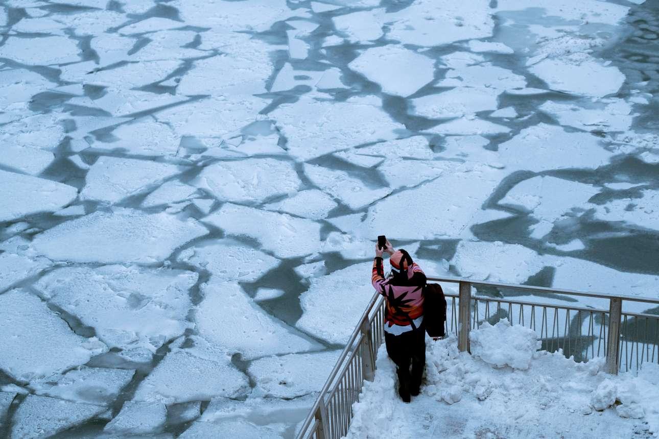 Εικόνα σαν από ταινία φαντασίας. Κάποιος φωτογραφίζει τον παγωμένο ποταμό του Σικάγου ενώ τα πόδια του βυθίζονται στο χιόνι