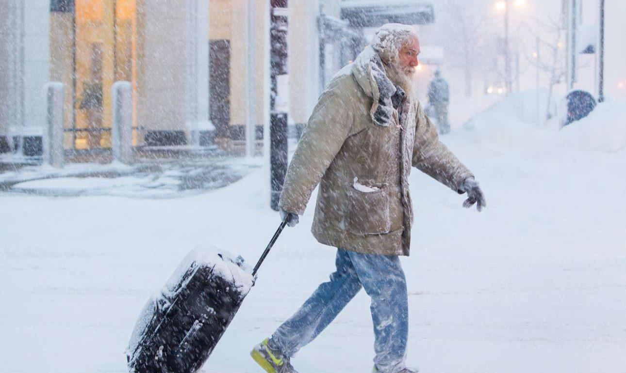 Ενας άνδρας προσπαθεί να σύρει την βαλίτσα του στο χιονισμένο Μπάφαλο της Νέας Υόρκης