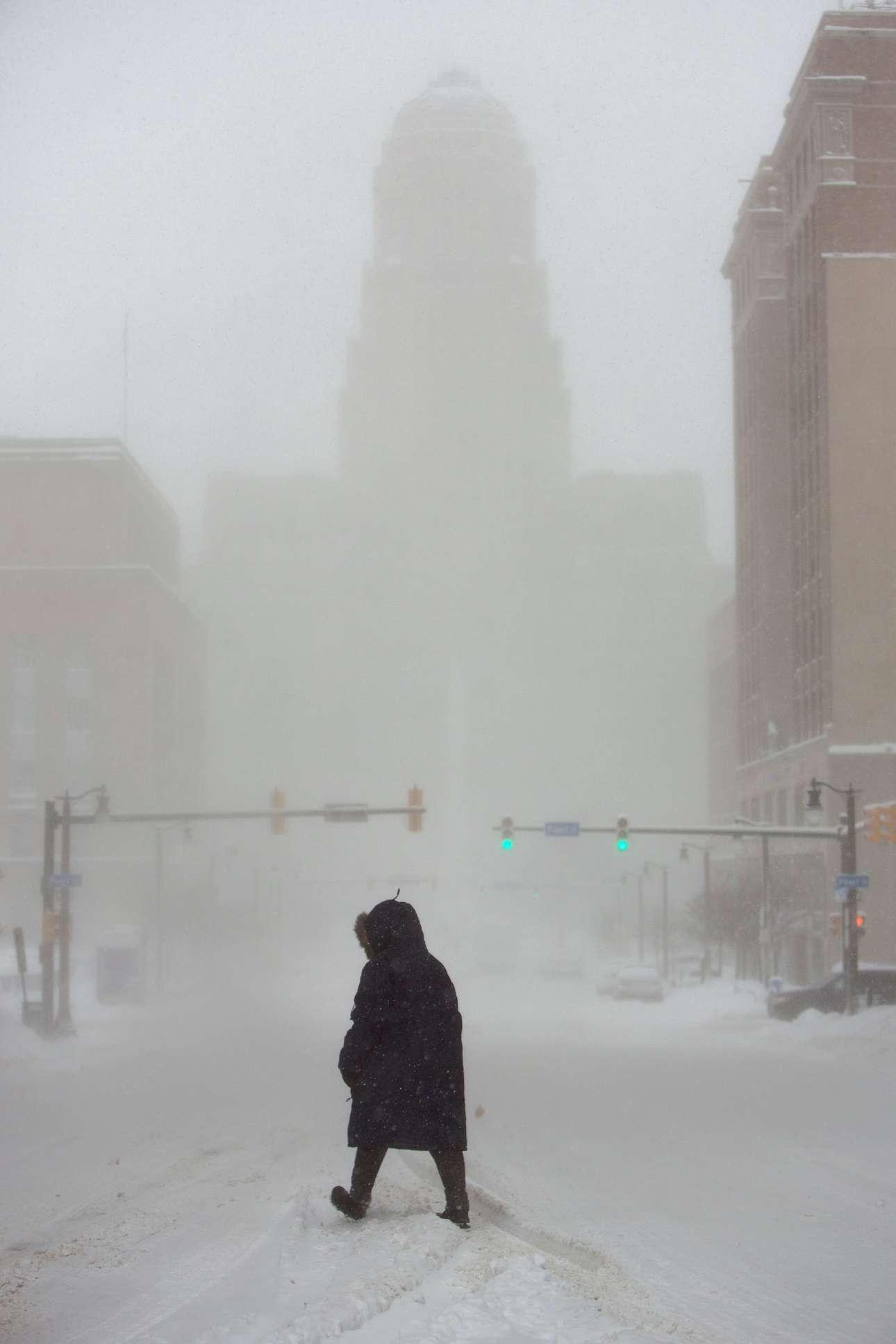 Εν μέσω χιονοθύελλας, μια γυναίκα διασχίζει λεωφόρο στο Μπάφαλο της Νέας Υόρκης