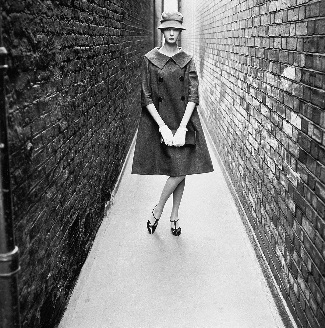 Φωτογραφία τραβηγμένη στο Λονδίνο για λογαριασμό της Vogue. Το μοντέλο φοράει παλτό από την πρώτη συλλογή του Ιβ Σεν Λοράν για τον οίκο, ο οποίος απέφυγε το σήμα κατατεθέν στιλ του Dior και προτίμησε πιο απαλές και ρευστές γραμμές