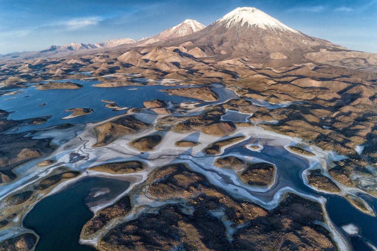Ο ήλιος δύει πάνω από τα ηφαίστεια Parinacota και Pomerape, στο Εθνικό Πάρκο Lauca της Χιλής
