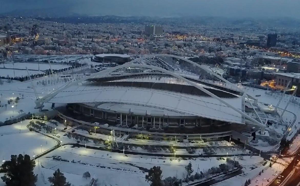 Το χιονισμένο ΟΑΚΑ με την περίφημη στέγη Καλατράβα, σε αεροφωτογραφία από drone. Στο βάθος το κτίριο του ΟΤΕ