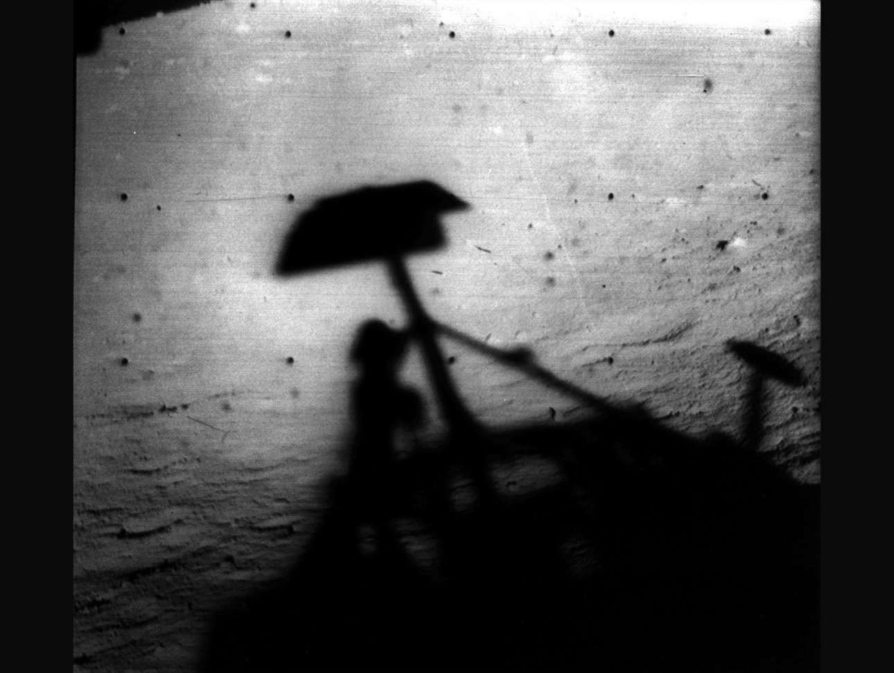 Η σκιά του Surveyor 1 της NASA πάνω στην επιφάνεια της Σελήνης. Το Surveyor 1 ήταν η πρώτη από τις αποστολές του Surveyor που έκανε μια επιτυχημένη μαλακή προσγείωση και απέδειξε την ορθότητα του σχεδιασμού και της τεχνικής προσγείωσης του διαστημικού οχήματος. Το Surveyor 1 εκτοξεύθηκε στις 30 Μαΐου 1966 και προσγειώθηκε στις 2 Ιουνίου 1966 και πέρα από τη μετάδοση 11.000 εικόνων, έστειλε επίσης πληροφορίες σχετικά με την αντοχή του σεληνιακού εδάφους, την ανακλαστικότητα του ραντάρ και τη θερμοκρασία