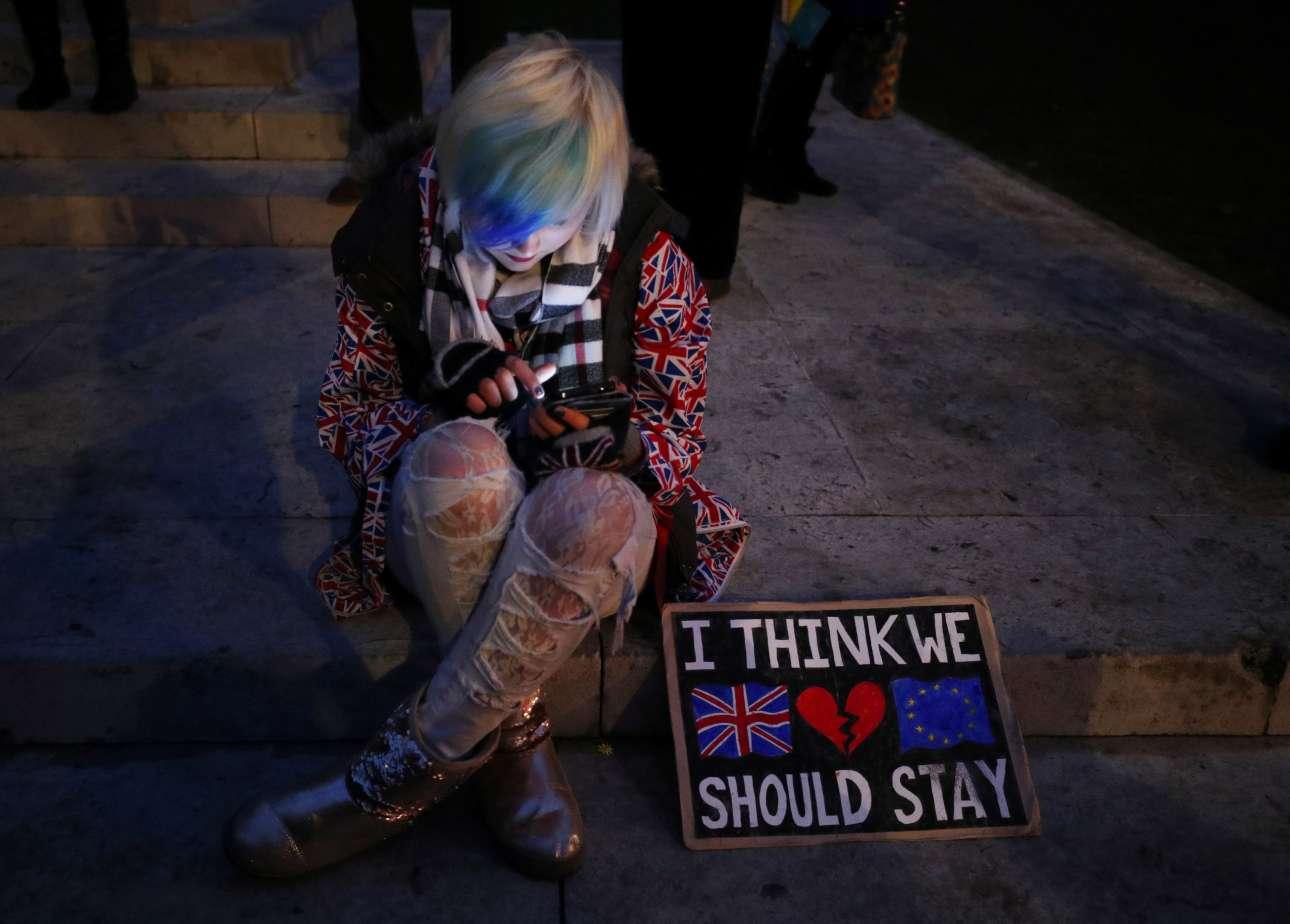 Τρίτη, 29 Ιανουαρίου, Αγγλία. Νεαρή Βρετανίδα ασχολείται με το κινητό της σε συγκέντρωση ενάντια στο Brexit, έξω από το Κοινοβούλιο, στο Λονδίνο. Το χαρτόνι δίπλα της γράφει: «Νομίζω ότι πρέπει να μείνουμε»