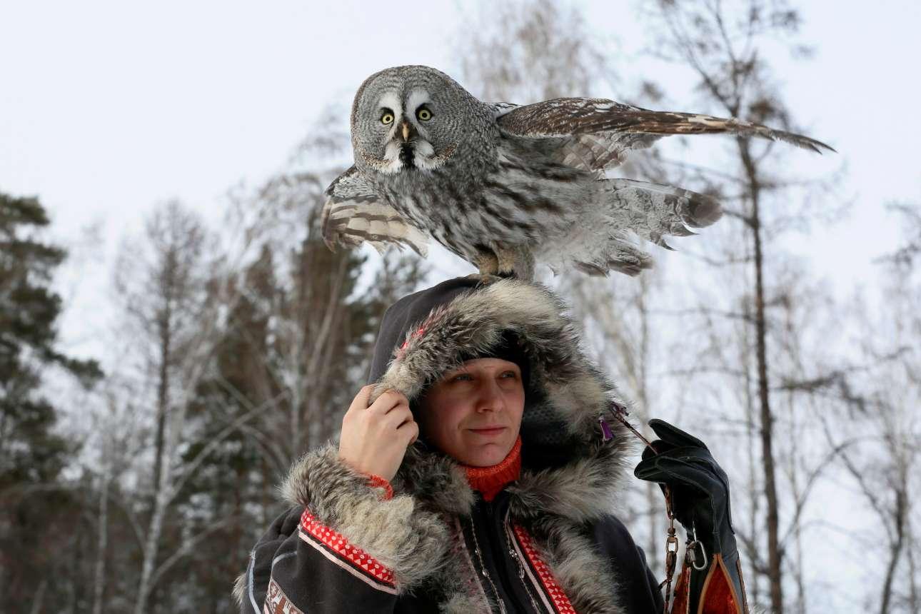 Τετάρτη, 30 Ιανουραρίου, Ρωσία. Μια κουκουβάγια κάθεται στο κεφάλι της εκπαιδεύτριάς της κατά τη διάρκεια επίδειξης σε δάσος του Κρασνογιάρσκ