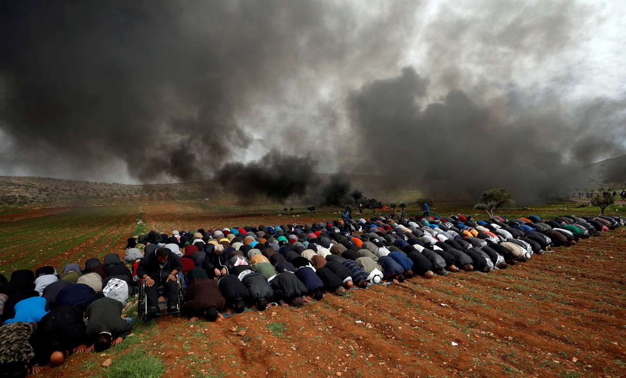 Παρασκευή, 1 Φεβρουαρίου, Δυτική Οχθη. Παλαιστίνιοι προσεύχονται καθώς μαύρος καπνός από καμένα λάστιχα αναδύεται σε χωριό κοντά στην Ραμάλα