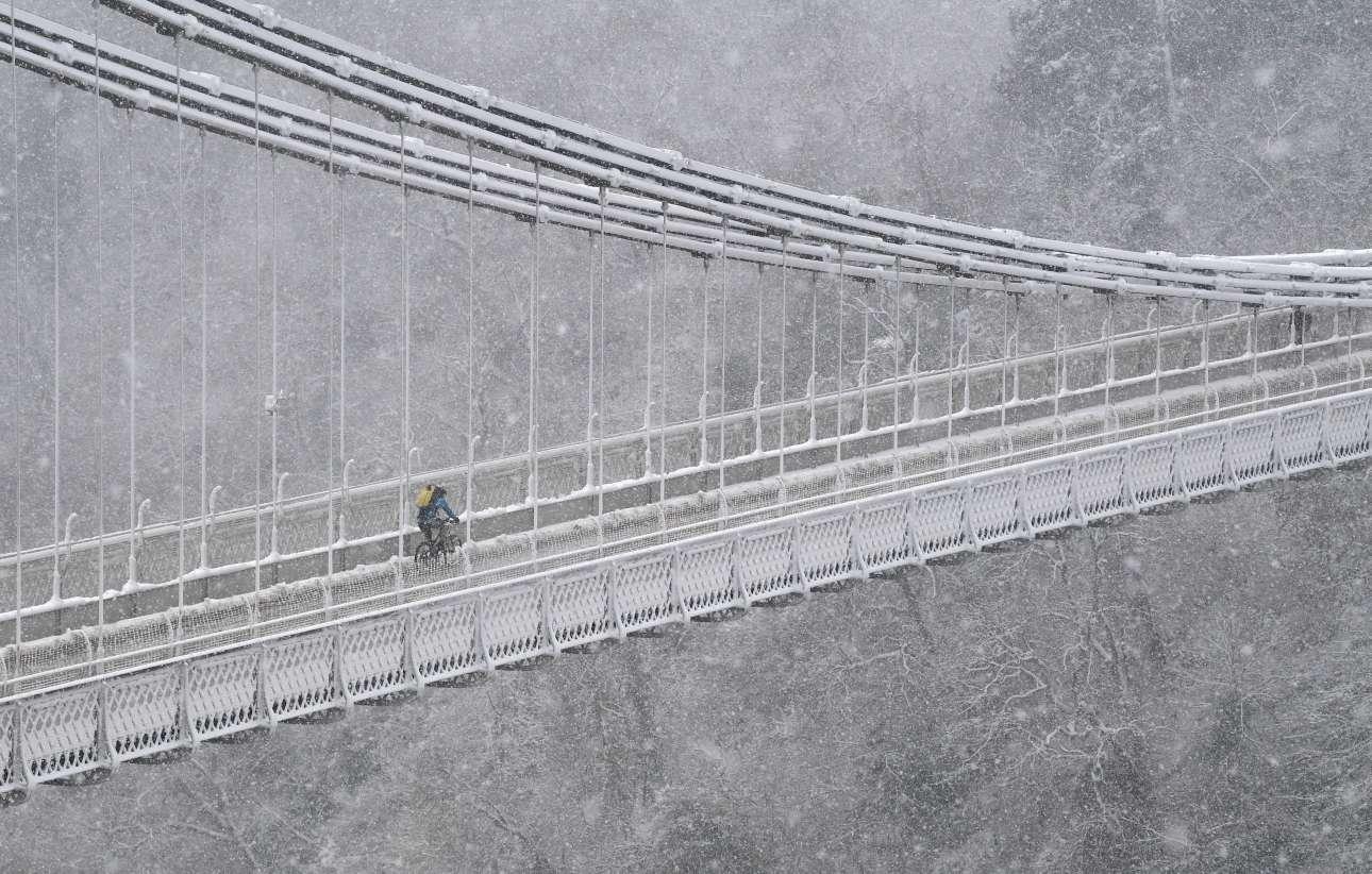 Παρασκευή, 1 Φεβρουαρίου, Αγγλία. Ενας ποδηλάτης διασχίζει την κρεμαστή γέφυρα του Μπρίστολ εν μέσω χιονόπτωσης.
