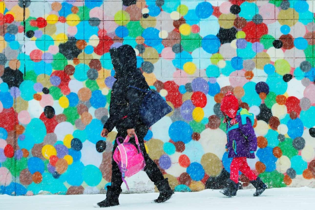 Τρίτη, 12 Φεβρουαρίου, ΗΠΑ. Μία γυναίκα περπατάει με το παιδί της κατά τη διάρκεια χιονόπτωσης στη Βοστόνη