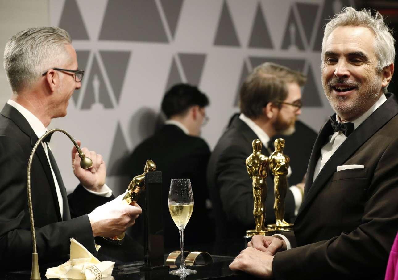 Ο Αλφόνσο Κουαρόν απολαμβάνει ένα ποτήρι σαμπάνιας καθώς περιμένει να χαράξουν το όνομά του για τα δύο Οσκαρ που κέρδισε για το «Roma» (Σκηνοθεσίας και Ξενόγλωσσης Ταινίας)