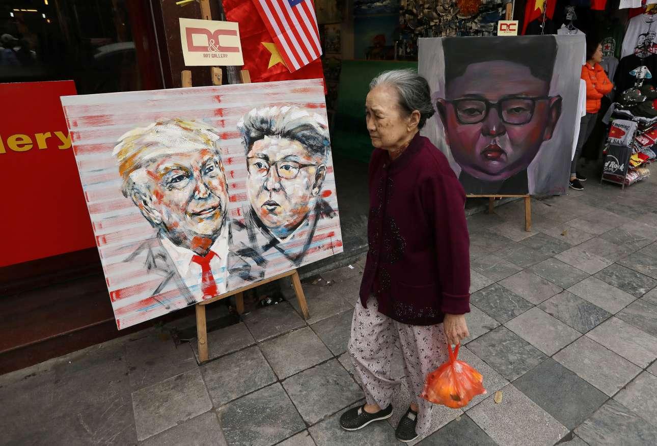 Ηλικιωμένη Βιετναμέζα περπατά δίπλα από πίνακα με τον Ντόναλντ Τραμπ και τον Κιμ Γιονγκ-ουν που περιμένει κάποιον αγοραστή