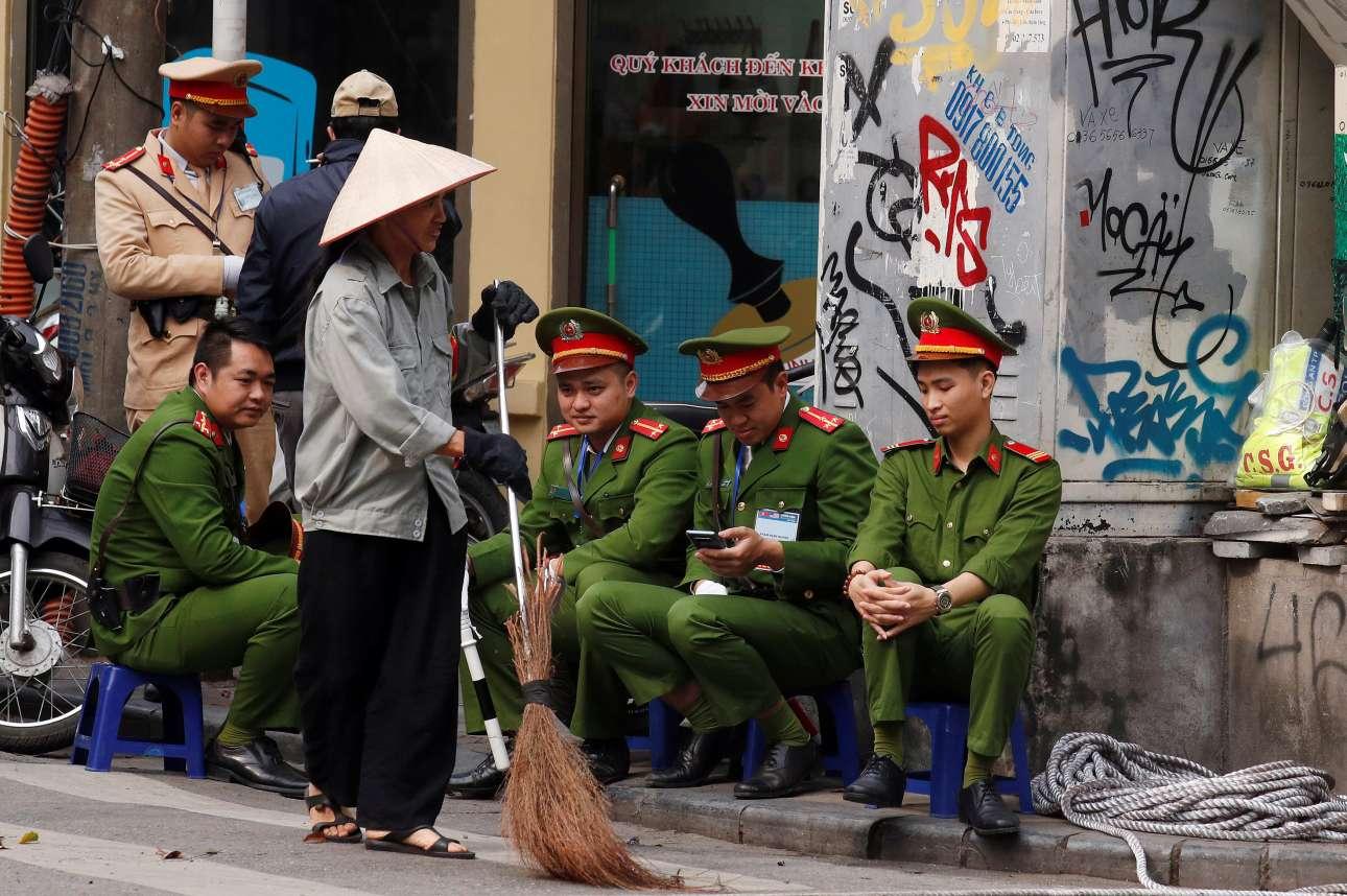 Βιετναμέζος με το παραδοσιακό του καπέλο («νον λα») καθαρίζει τον δρόμο υπό το βλέμμα αστυνομικών
