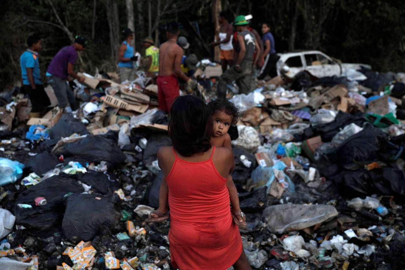 Παρασκευή, 1 Μαρτίου, Βενεζουέλα. Η 17χρονη Αστρίντ Πράντο, έγκυος στον έβδομο μήνα, κρατάει το γιο της Τζεσουάνι καθώς περιμένει τον άντρα της ο οποίος μαζί με άλλους αναζητούν ανακυκλώσιμα υλικά σε χωματερή στην περιοχή Πακαραΐμα
