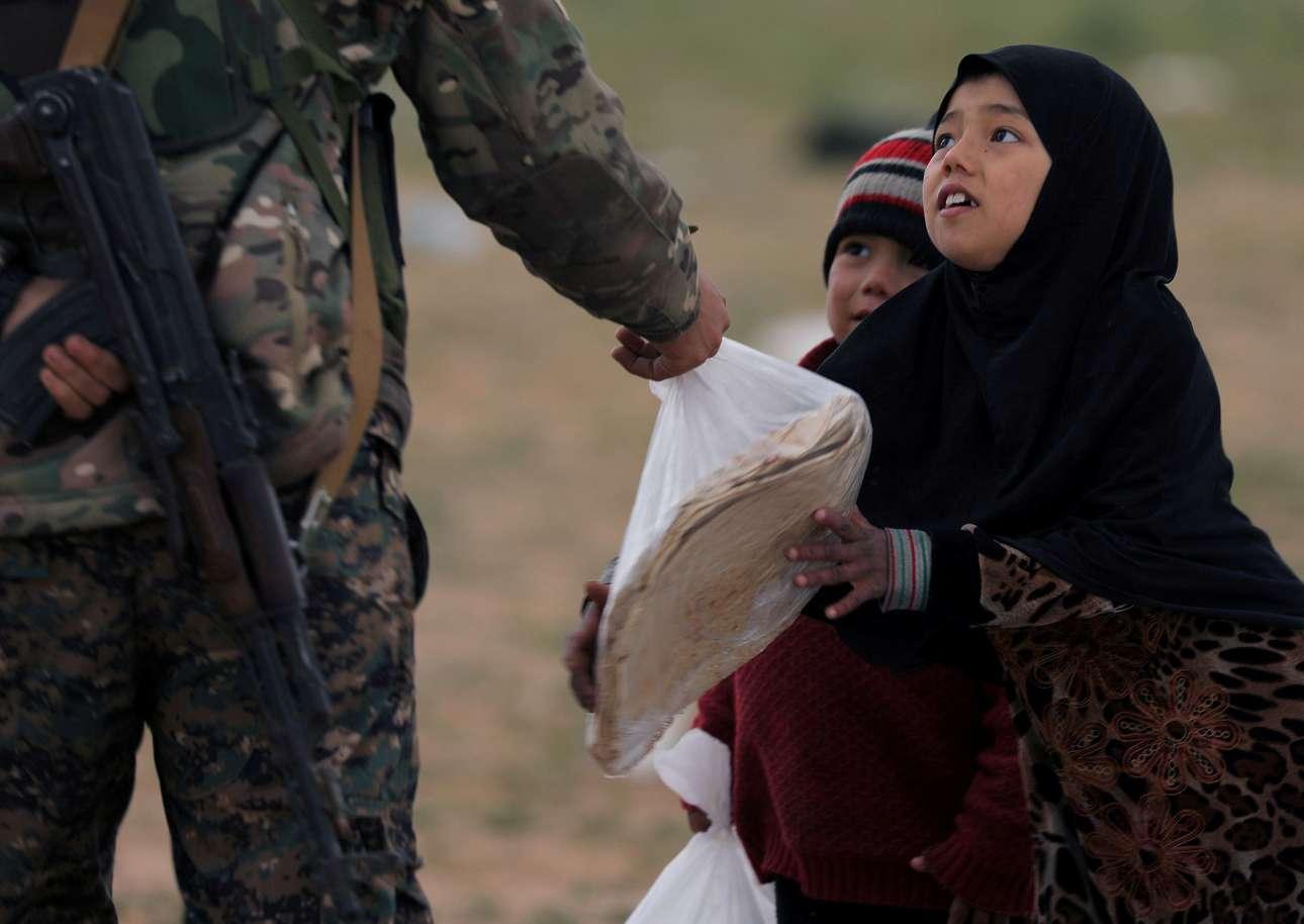 Τετάρτη, 27 Φεβρουαρίου, Συρία. Ενα κορίτσι παίρνει μία σακούλα με ψωμί από στρατιώτη των Συριακών Δημοκρατικών Δυνάμεων (SDF) σε περιοχή κοντά στο χωριό Μπαγκούζ