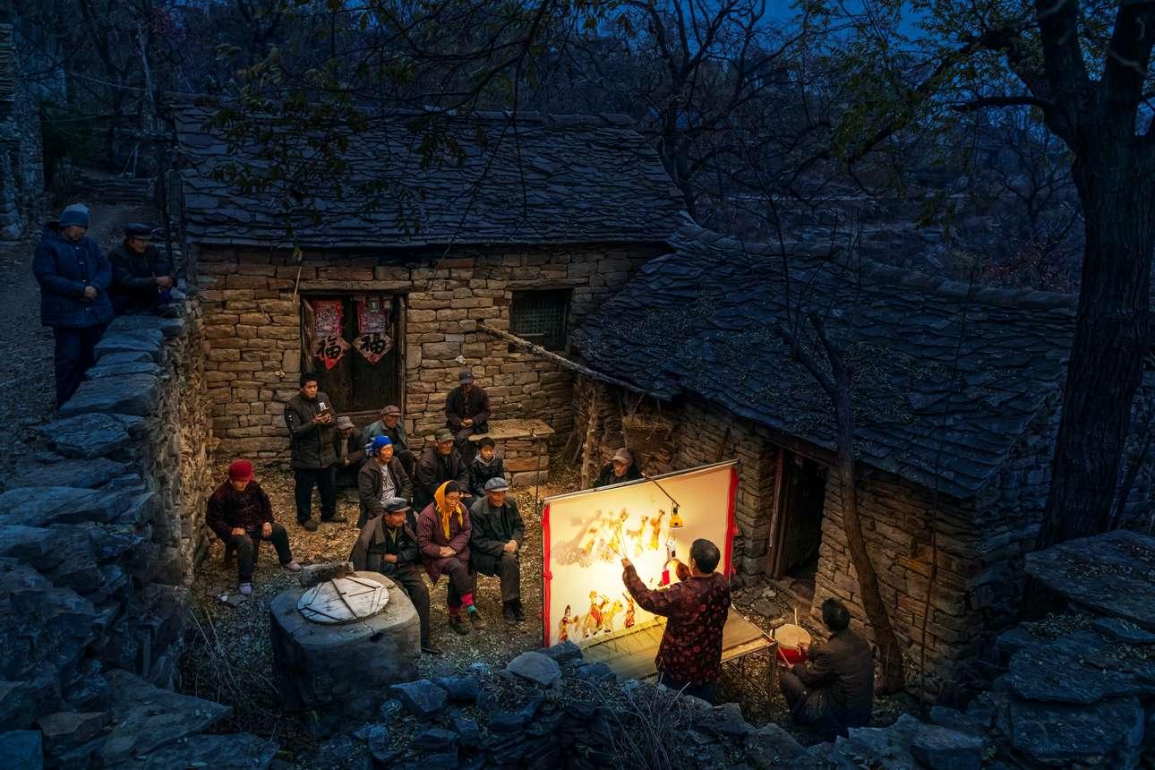 «Κουκλοθέτρο». Θέατρο σκιών, μια αρχαία παράδοση 2.000 ετών, στην αυλή ενός πέτρινου σπιτιού σε μικρό χωριό της Κίνας