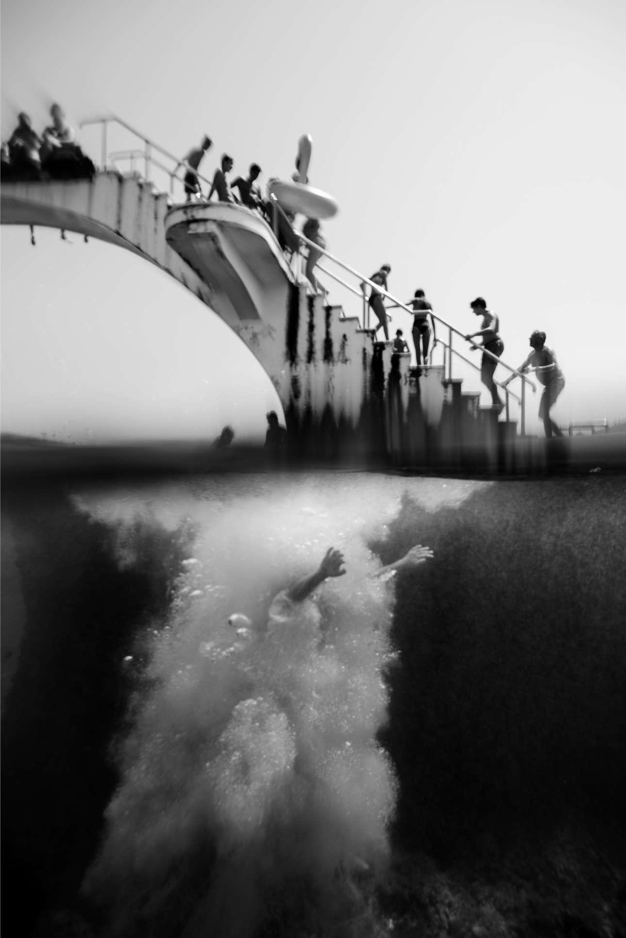 «Τα Χέρια»: άνδρας βουτάει από βατήρα σε πολυσύχναστη παραλία της Ρόδου. Με την παραπάνω εικόνα ο Φίλιππος Αλαφάκης κέρδισε το Εθνικό Βραβείο εκπροσωπώντας την Ελλάδα