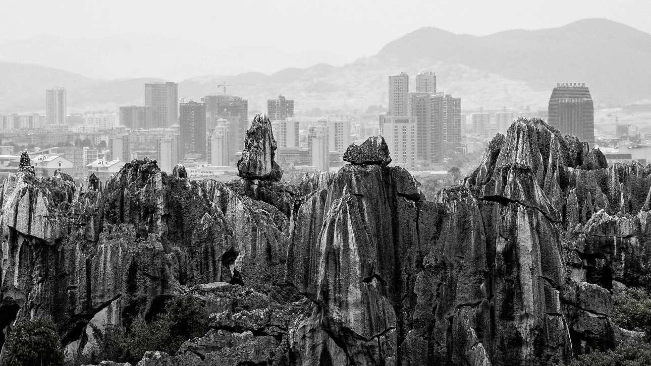 Πρώτη θέση στην κατηγορία Φωτογραφία Δρόμου. Το πέτρινο δάσος που έχει δημιουργηθεί με τα χρόνια λόγω διάβρωσης στη Νότια Κίνα «μοιάζει να συμμετέχει σε έναν σιωπηλό διάλογο με τους ουρανοξύστες που έχουν σχεδιάσει οι άνθρωποι»