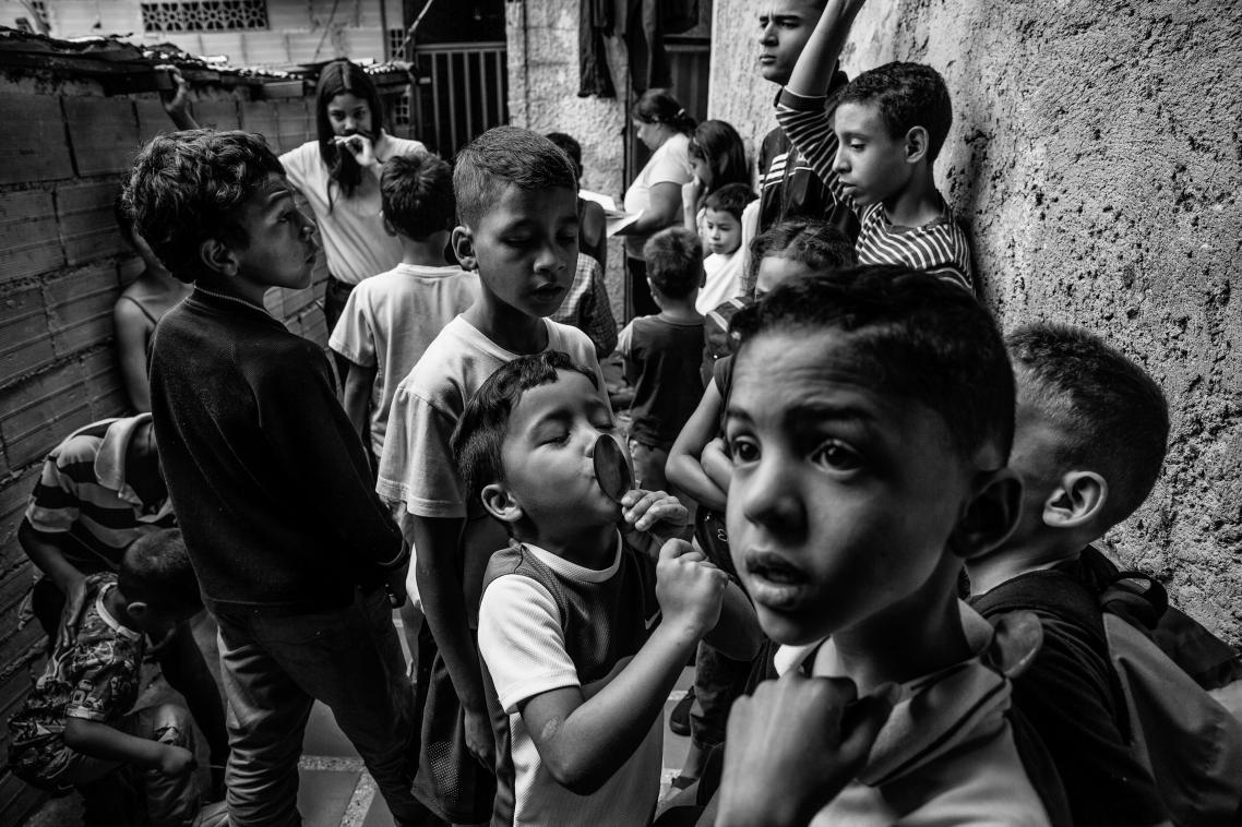 Αγοράκι φιλάει το κουτάλι του καθώς περιμένει έξω από κοινωνικό συσσίτιο στο Καράκας. Η παραπάνω εικόνα αποτελεί μέρος φωτογραφικής σειράς που διηγείται την ιστορία μίας χώρας που καταρρέει