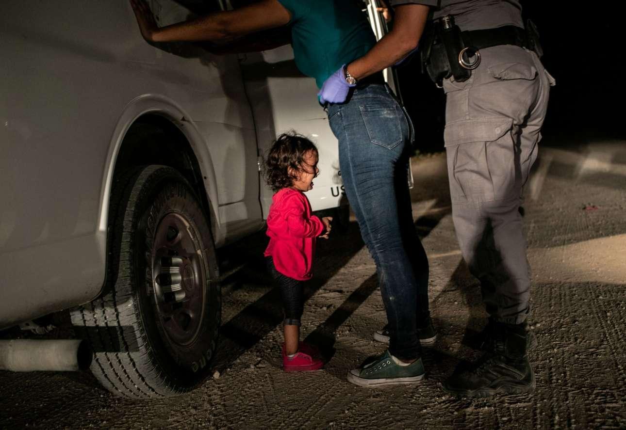 Η δίχρονη Γιάνα από την Ονδούρα κλαίει καθώς ένας φύλακας κάνει σωματικό έλεγχο στη μητέρα της στα σύνορα Μεξικού - ΗΠΑ, στο Τέξας. (Από το ενσταντανέ αυτό το αμερικανικό περιοδικό Τime πήρε τη φιγούρα της μικρής και συνέθεσε ένα κολάζ με τον πρόεδρο Τραμπ, βλοσυρότατο κέρβερο της πατρίδας, σε εξώφυλλό του τον Ιούνιο του 2018 – o τίτλος του ήταν ειρωνικός: Welcome to America)