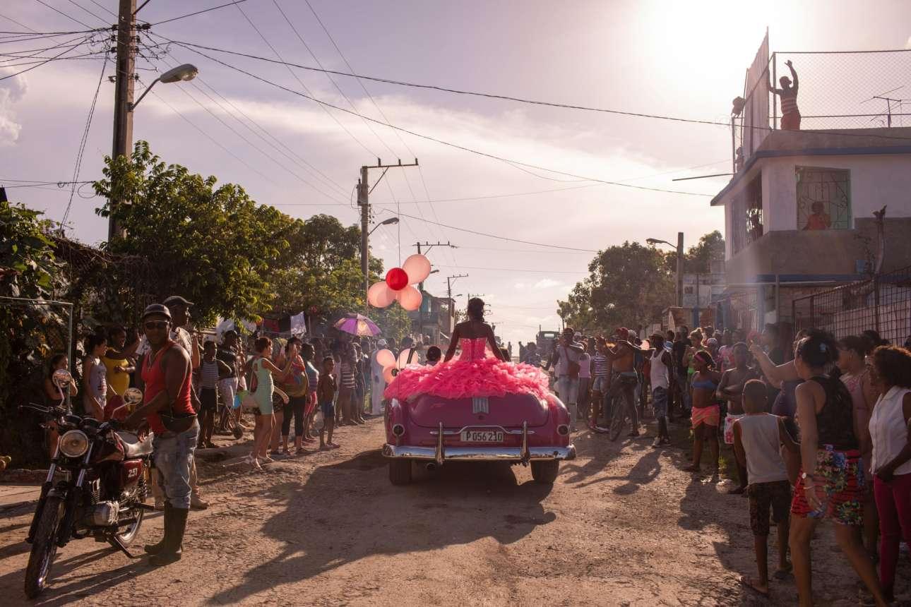 Ντυμένη στα ροζ, ασορτί με το κάμπριο αυτοκίνητο, η Πούρα παρελαύνει στη γειτονιά της στην Αβάνα, καθώς η κοινότητα συγκεντρώνεται για να γιορτάσει τα 15α γενέθλιά της