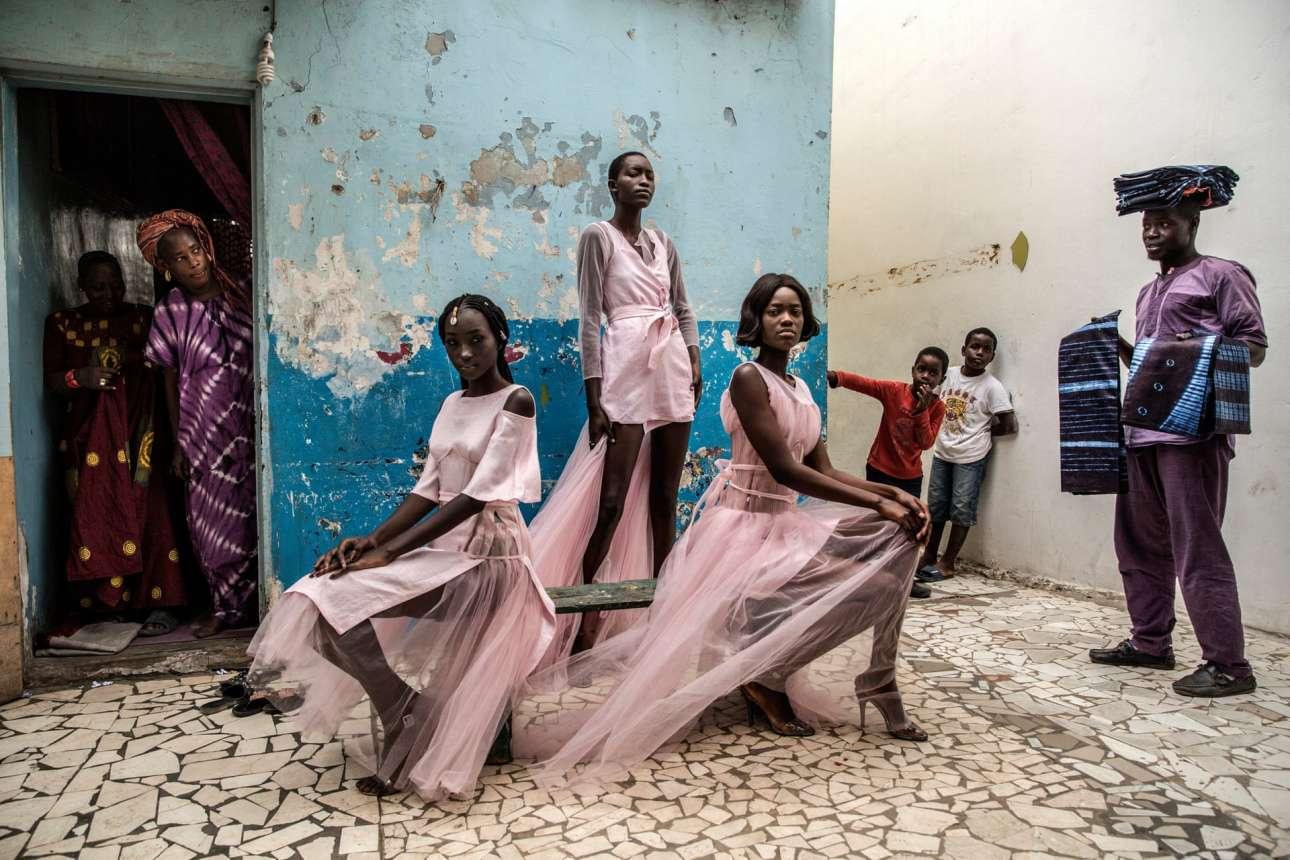 Μοντέλα με ρούχα του σενεγαλέζου σχεδιαστή Αντάμα Πάρις ποζάρουν και τραβούν τα βλέμματα ακόμα και των παιδιών στη γειτονιά Μεντίνα του Ντακάρ