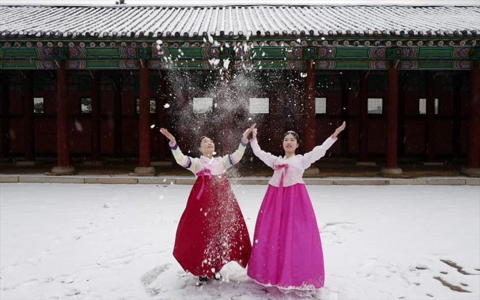 Παρασκευή, 15 Φεβρουαρίου. Νότια Κορέα. Κινέζες τουρίστριες φορώντας παραδοσιακά νοτιοκορεάτικα φορέματα, γνωστά ως χάνμποκ, φωτογραφίζονται στο χιονισμένο παλάτι Γκιόνγκμποκουνγκ, στη Σεούλ