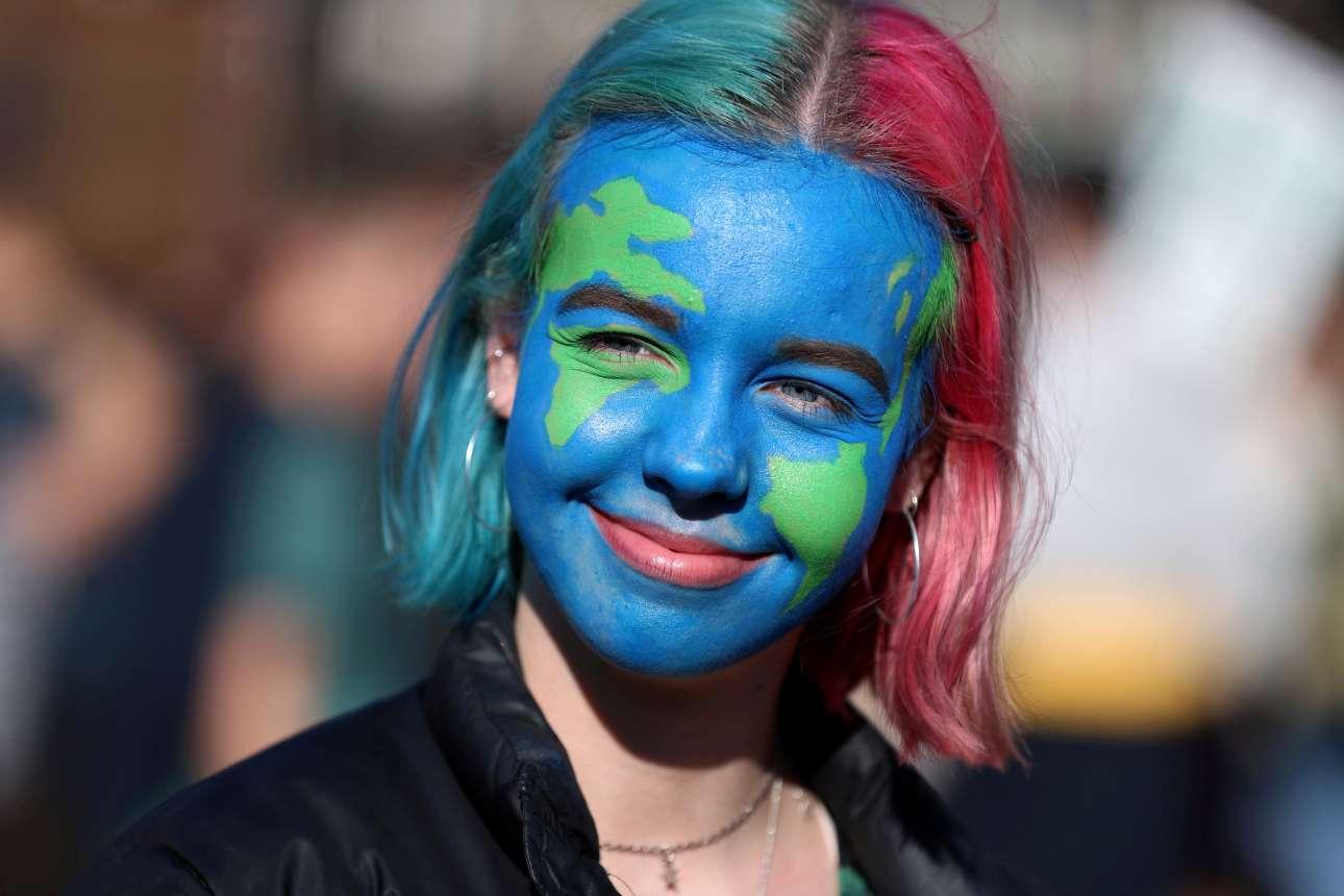 Εχοντας ζωγραφισμένη στο πρόσωπό της τη Γη, μία μαθήτρια παρακολουθεί τις διαδηλώσεις στο Λονδίνο