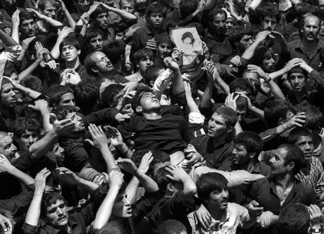 Το πλήθος στην Τεχεράνη κρατά στα χέρια του έναν άνδρα ενώ χιλιάδες περιμένουν να αποτίσουν ύστατο φόρο τιμής στον Αγιατολάχ Χομεϊνί μετά τον θάνατό του τον Ιούνιο του 1989