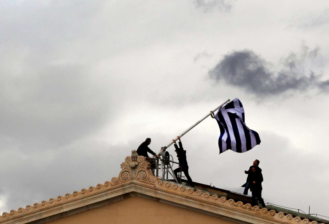 Άλλη μια εμβληματική και πολυχρησιμοποιημένη φωτογραφία της ελληνικής κρίσης. Εργαζόμενοι της Βουλής αντικαθιστούν τη σημαία πάνω στο κτίριο, τον Απρίλιο του 2012