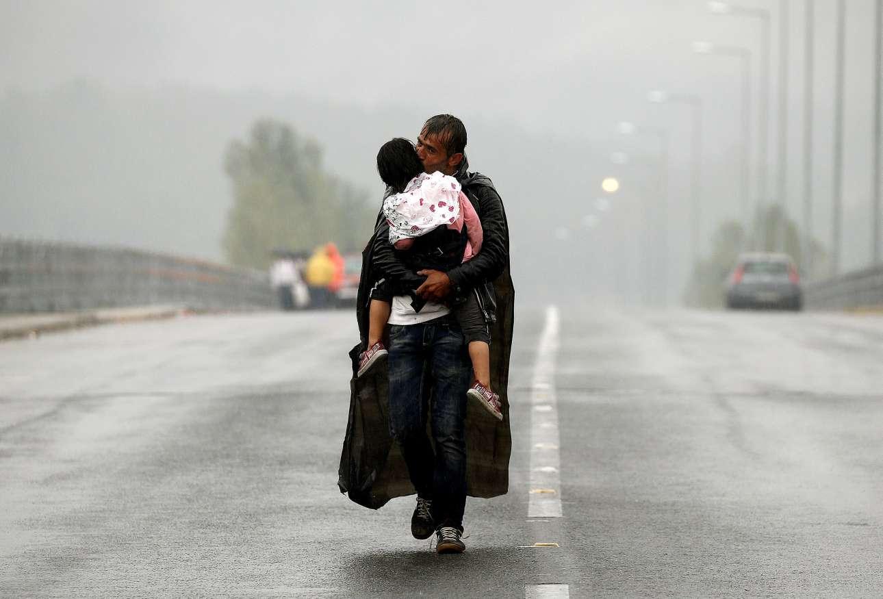 Ισως η πιο γνωστή και πιο δυνατή φωτογραφία του Γιάννη Μπεχράκη: πρόσφυγας από τη Συρία με την κορούλα του περπατά μέσα στην βροχή στην Ειδομένη, καθ΄οδόν προς τα σύνορα, στις 10 Σεπτεμβρίου 2015