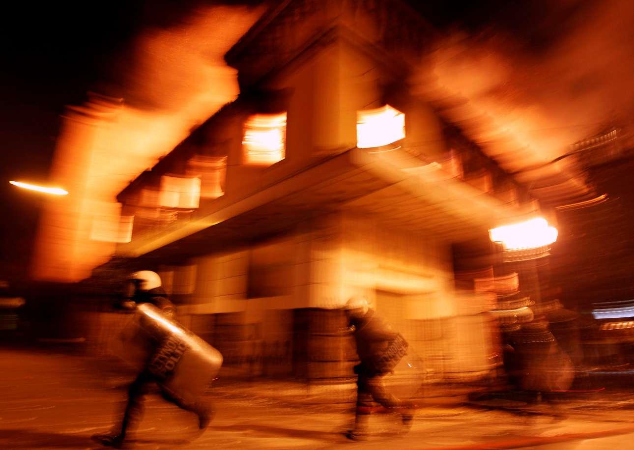 Αστυνομικοί μπροστά στον καιγόμενο κινηματογράφο «Αττικόν» στην Αθήνα, κατά τα επεισόδια της 12ης Φεβρουαρίου 2012