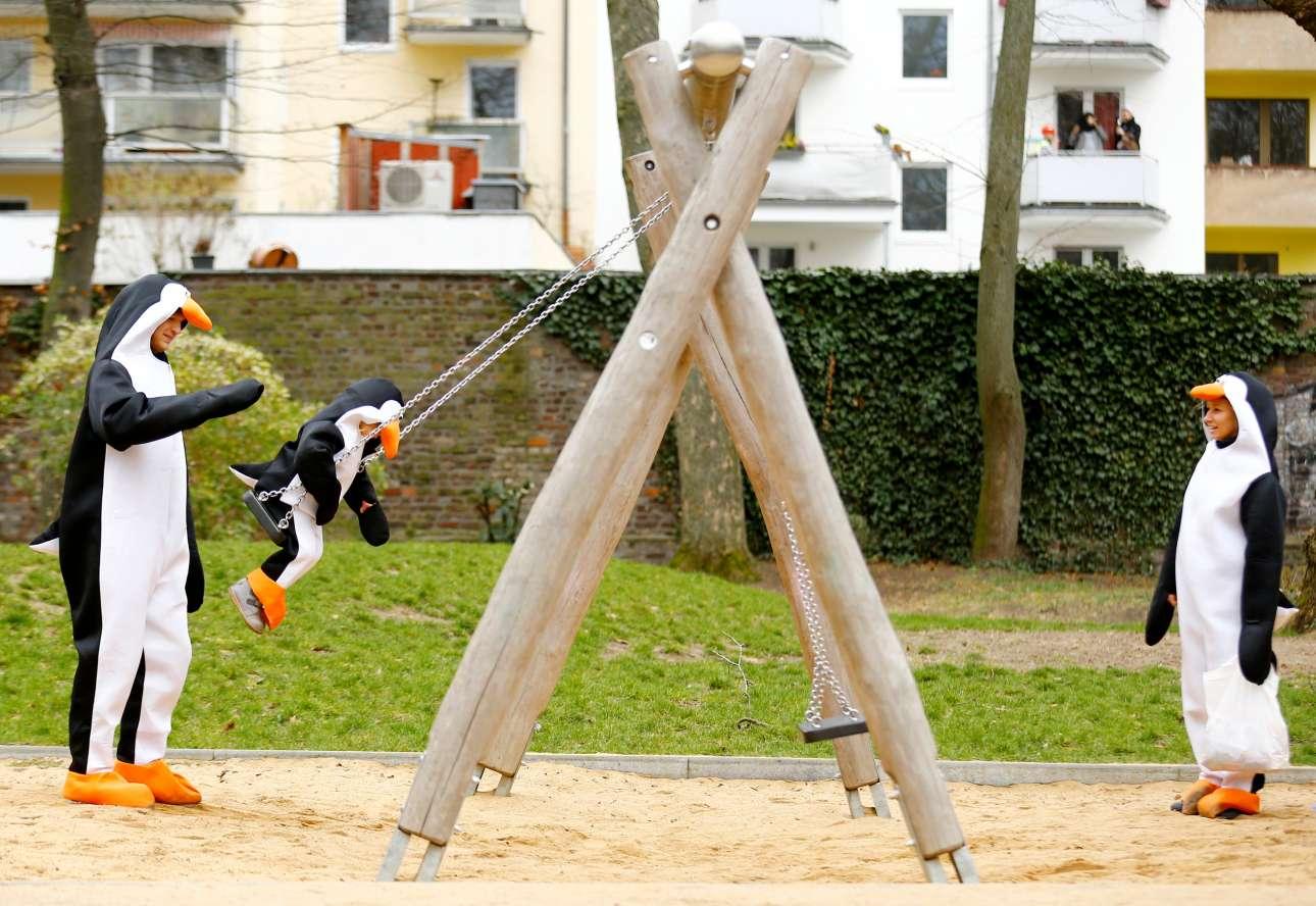 Δευτέρα, 4 Μαρτίου, Γερμανία. Τα μέλη μιας οικογένειας ντυμένα με στολές πιγκουίνων παίζουν στην παιδική χαρά Rosenmontag (Ροζ Δευτέρα) στην Κολωνία