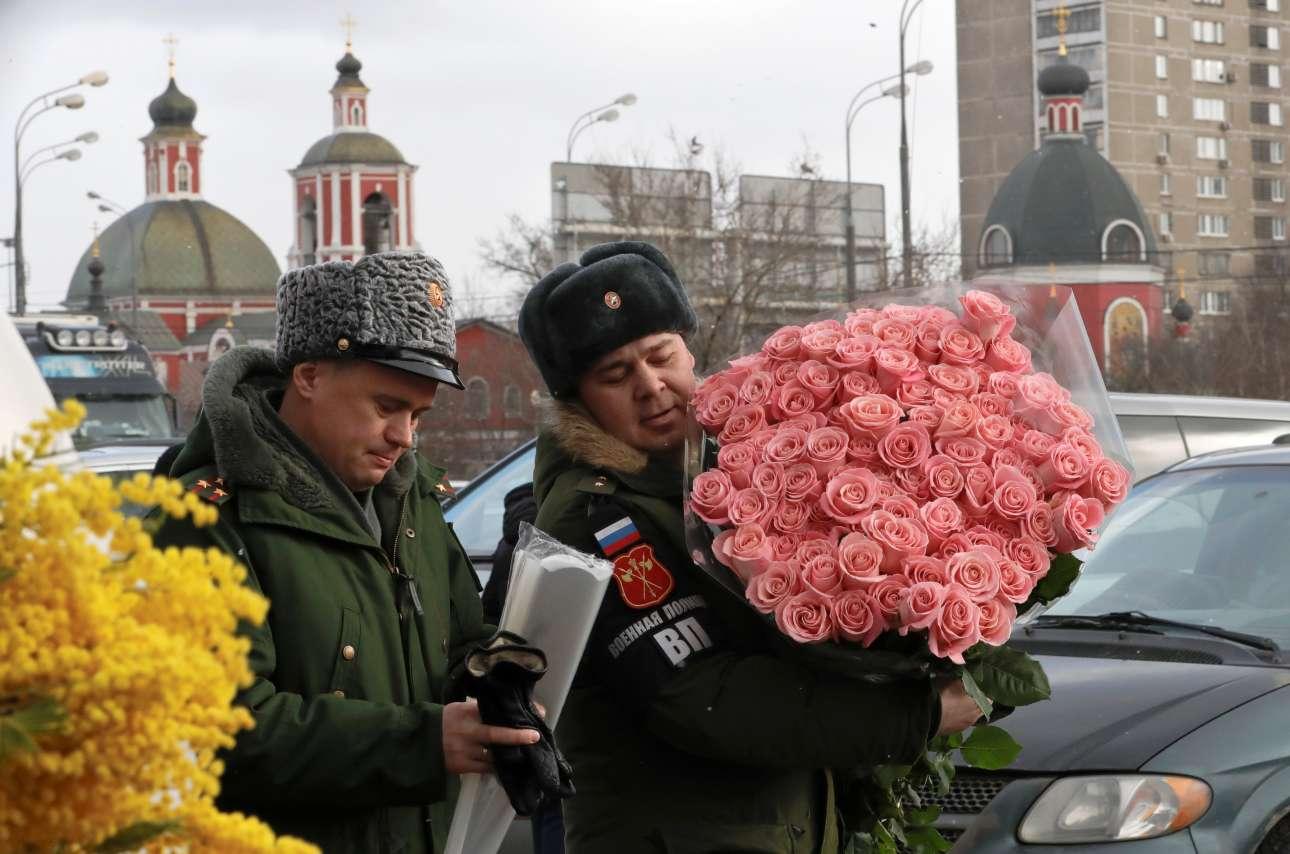 Αξιωματικός του ρωσικού στρατού κρατά ένα μεγάλο μπουκέτο λουλούδια που προορίζει για κάποια γυναίκα της ζωής του, στη Μόσχα, την Ημέρα της Γυναίκας