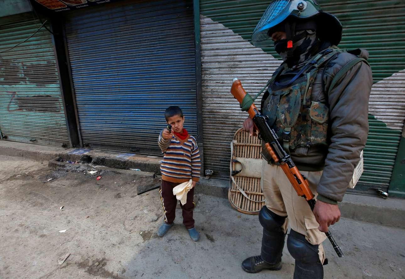Παρασκευή, 8 Μαρτίου, Ινδία. Ο μικρός και ο μεγάλος πολεμιστής. Μικρό αγόρι κάνει ότι πυροβολεί με ένα όπλο-παιχνίδι υπό το βλέμμα ένοπλου αστυνομικού σε δρόμο της Σριναγκάρ - θερινής πρωτεύουσας της ινδικής ομόσπονδης πολιτείας Τζαμού και Κασμίρ