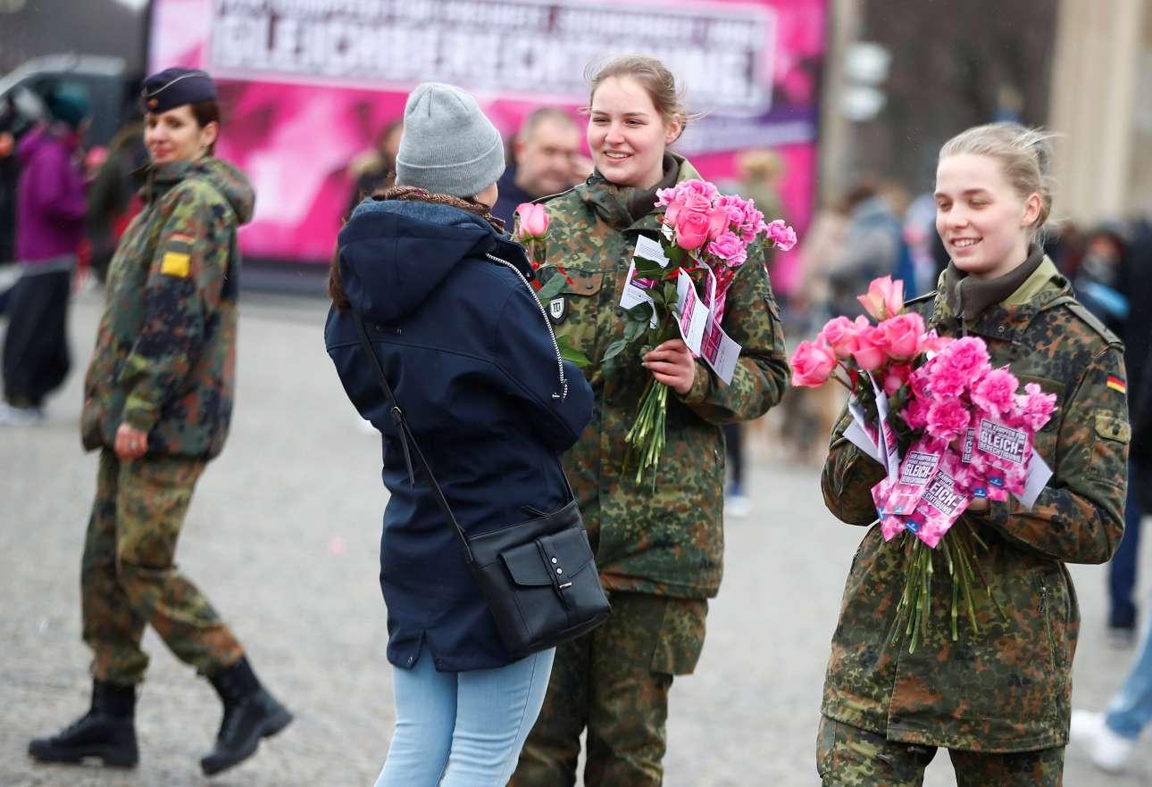 Γερμανίδες, μέλη των ενόπλων δυνάμεων, μοιράζουν λουλούδια στις περαστικές μπροστά στην Πύλη του Βραδεμβούργου, στο Βερολίνο