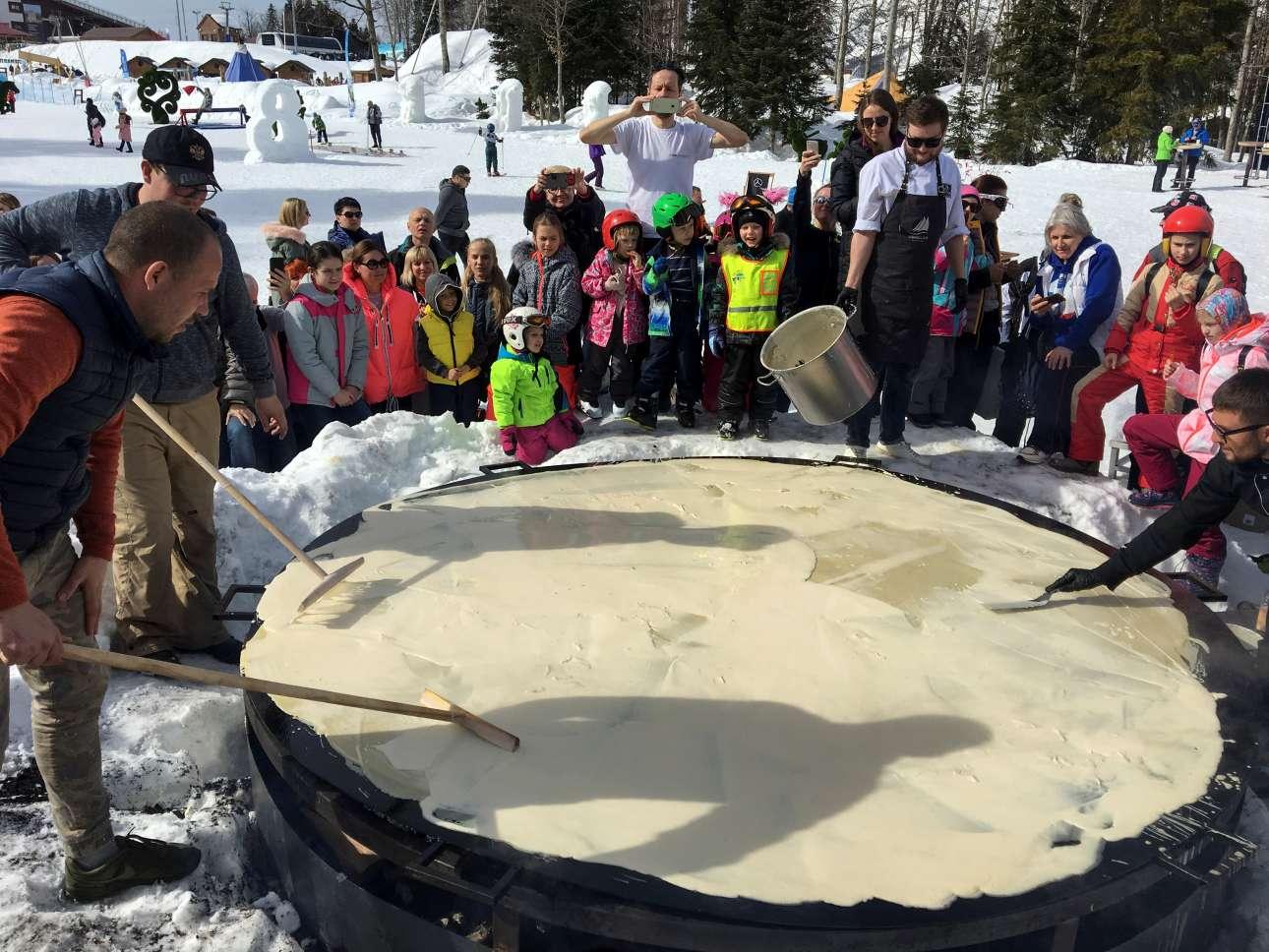 Μία τεράστια κρέπα τριών μέτρων ψήνεται έξω από το Σότσι. Οι στρογγυλές, ζεστές τηγανίτες και κρέπες αποτελούν το κύριο φαγητό της Μασλένιτσα, καθώς συμβολίζουν τον ήλιο