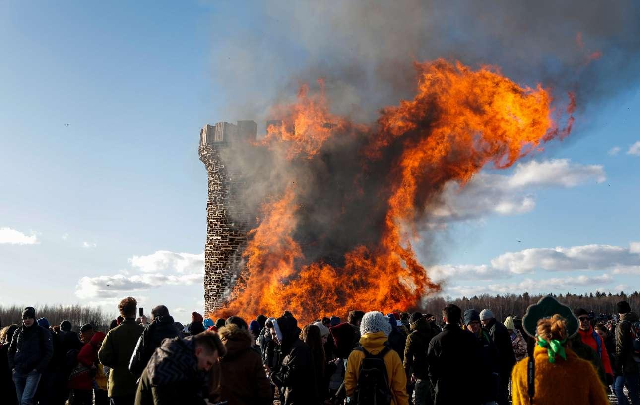 Ανθρωποι παρακολουθούν έναν πύργο από ξύλινες παλέτες να τυλίγεται στις φλόγες...