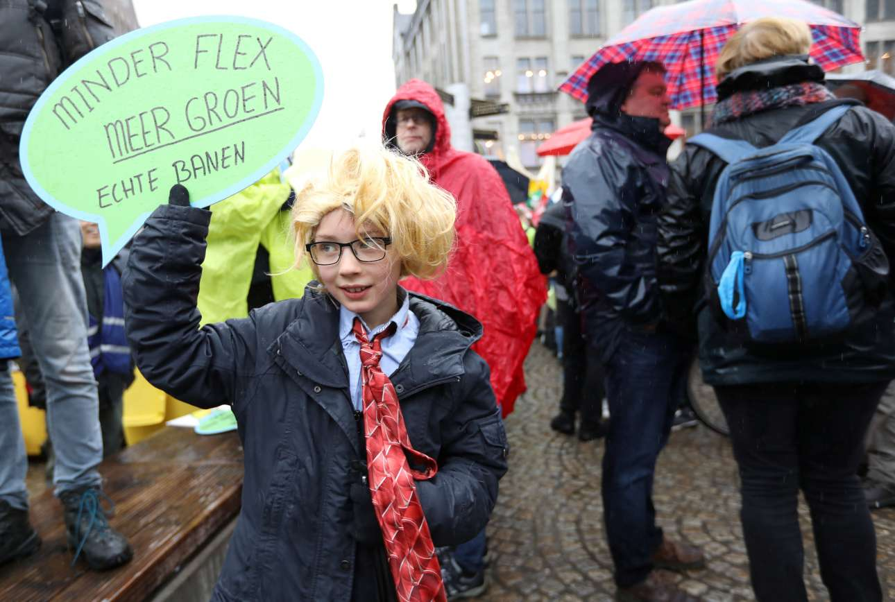 Ενα παιδάκι ντυμένο άνδρας κρατάει πλακάτ που γράφει «λιγότερη ελαστική εργασία και περισσότερο πράσινο, αυτό είναι πραγματική δουλειά» και διαδηλώνει στο κέντρο του Αμστερνταμ